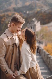 Belle giovani coppie che mostrano affetto sulla grande muraglia cinese