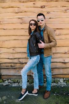 Belle giovani coppie che posano sopra la parete di legno