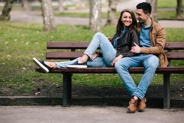 Belle giovani coppie che si distendono su una panchina nel parco