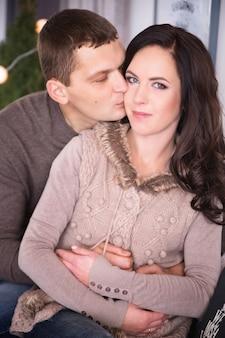 Belle giovani coppie che si rilassano in un salone con l'albero di nuovo anno