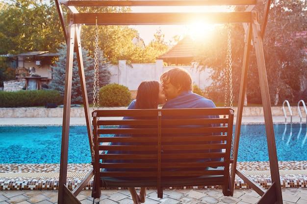 Belle giovani coppie che si siedono in panchina a bordo piscina