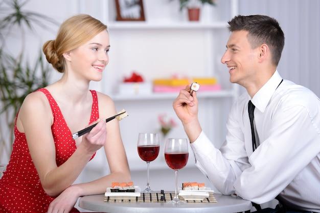 Belle giovani coppie che si siedono insieme al ristorante.