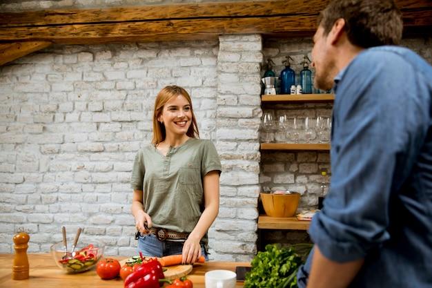 Belle giovani coppie che sorridono mentre cucinando nella cucina a casa