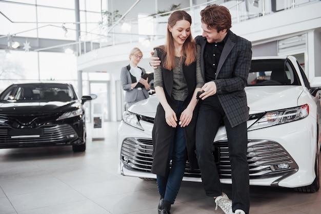 Belle giovani coppie che stanno alla concessionaria che sceglie l'auto per comprare