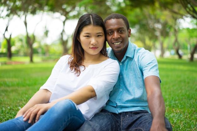 Belle giovani coppie interrazziali calme positive che esaminano macchina fotografica mentre riposando sull'erba