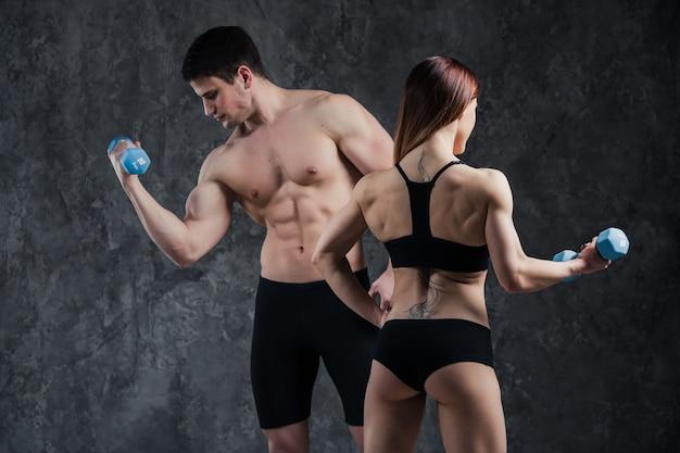 Belle giovani coppie sexy atletiche che posano nello studio