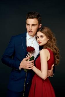 Belle giovani coppie sexy degli amanti della donna e dell'uomo su una parete nera