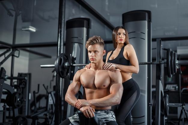 Belle giovani coppie sexy sportive che mostrano muscolo e allenamento in palestra durante il photoshooting