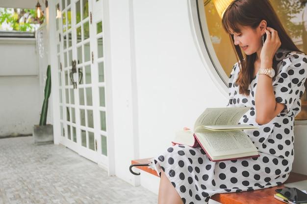 Belle giovani donne asiatiche che si siedono il libro di lettura all'aperto