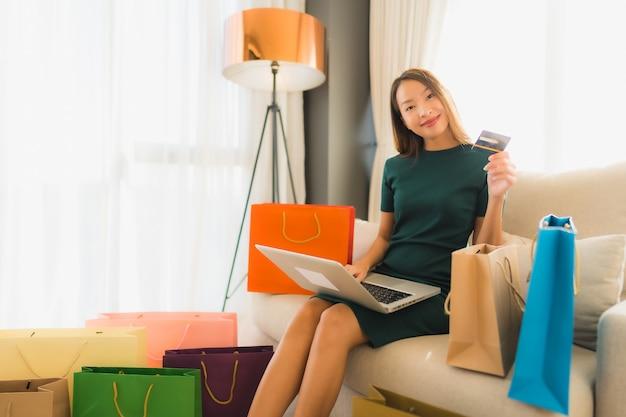 Belle giovani donne asiatiche del ritratto che per mezzo del computer portatile del computer con la carta di credito per acquisto online