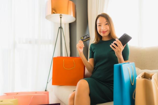 Belle giovani donne asiatiche del ritratto che per mezzo del telefono cellulare con la carta di credito per acquisto online