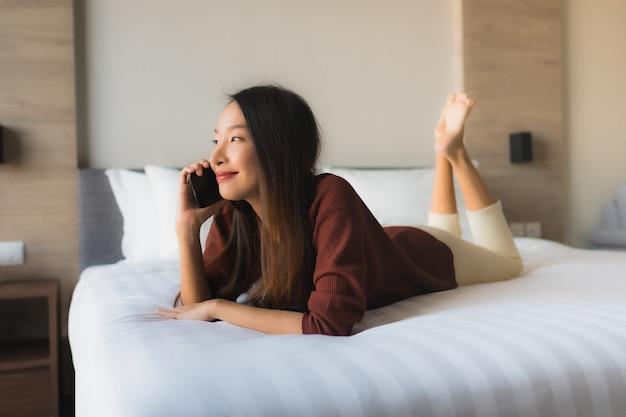Belle giovani donne asiatiche del ritratto che per mezzo del telefono cellulare sul letto