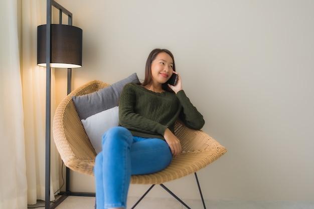 Belle giovani donne asiatiche del ritratto che usando telefono cellulare parlante e sedendosi sulla sedia del sofà