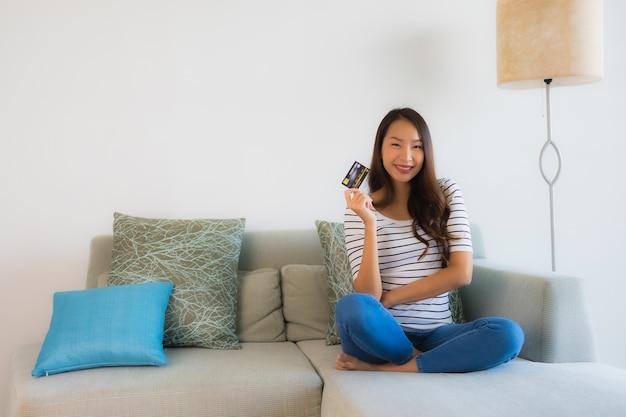 Belle giovani donne asiatiche del ritratto con il telefono cellulare o il computer della carta di credito per comperare
