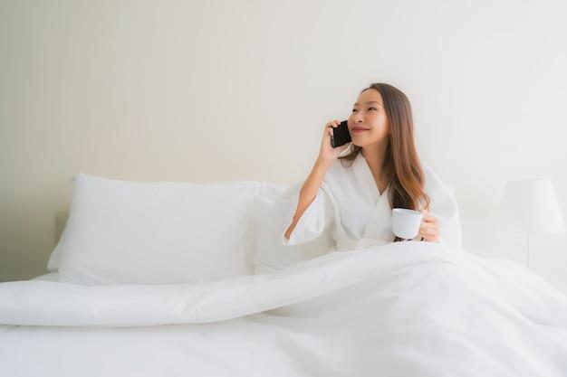 Belle giovani donne asiatiche del ritratto con la tazza e il telefono cellulare di caffè sul letto