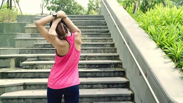 Belle giovani donne asiatiche dell'atleta in abbigliamento sportivo gambe riscaldamento e stretching lei braccia