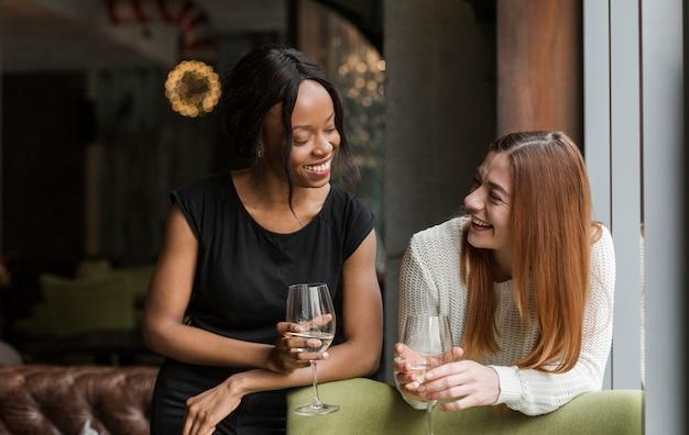 Belle giovani donne che mangiano vino insieme