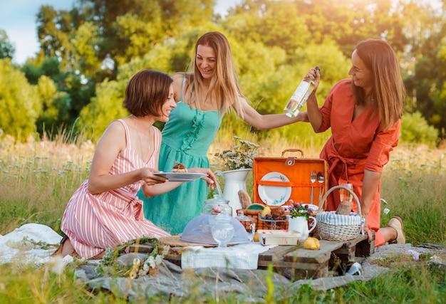 Belle giovani donne delle ragazze della ragazza su un picnic nel divertimento di estate per celebrare e bere vino.