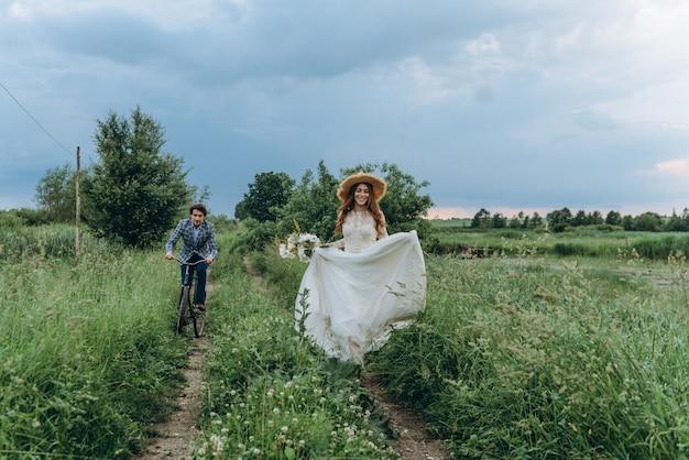 Belle giovani sposi delle coppie che camminano in un campo con una bicicletta