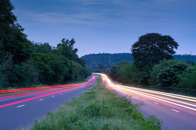 Belle luci di coda e la luce di testa di un'auto passano su una collina di strada campestre
