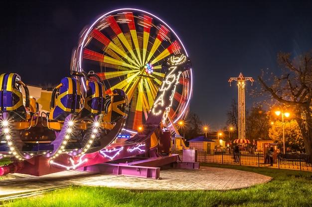 Belle luci di regime su giostre al parco divertimenti. gomel, belar