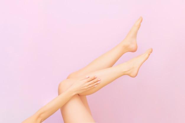Belle lunghe gambe femminili con pelle liscia dopo la depilazione su rosa pastello