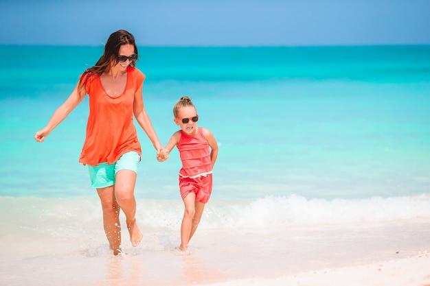Belle madre e figlia alla spiaggia caraibica che godono delle vacanze estive.
