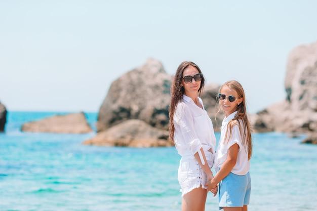 Belle madre e figlia in spiaggia godendo le vacanze estive.