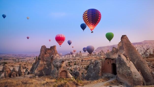 Belle mongolfiere che sorvolano il paesaggio della cappadocia all'alba