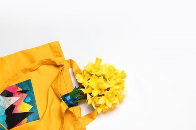 Belle narcisi gialli con una borsa di cotone giallo sullo sfondo