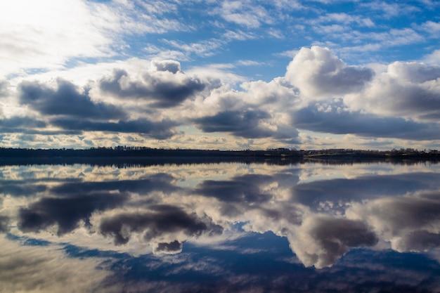 Belle nuvole sul cielo blu e riflesso nell'acqua