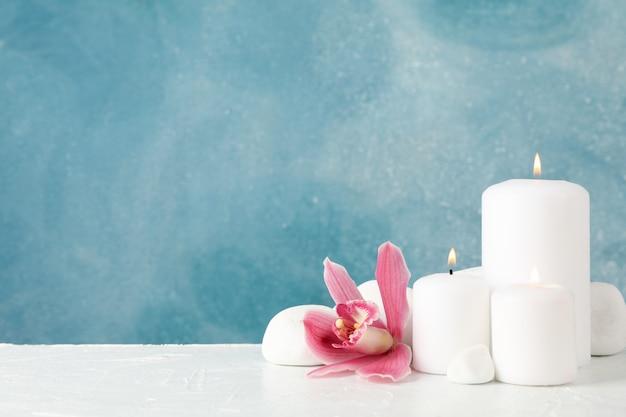 Belle orchidea, candele e pietre della stazione termale sulla tavola bianca, spazio per testo