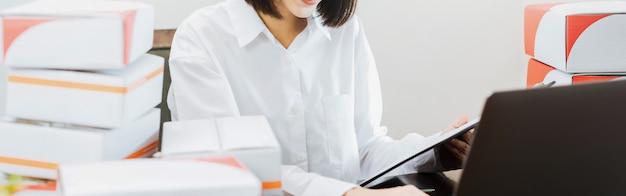 Belle parentesi graffe sorridenti della donna facendo uso del computer portatile che controllano ordine per il cliente e la consegna online.