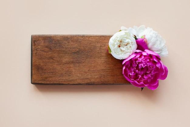 Belle peonie rosa e bianche su un fondo di legno
