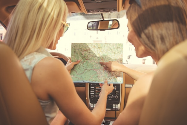 Belle ragazze alla moda che studiano la mappa durante il viaggio.