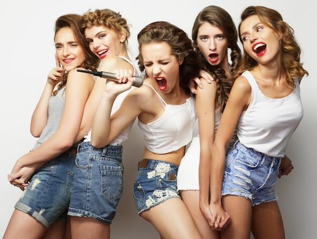 Belle ragazze alla moda hipster che cantano karaoke