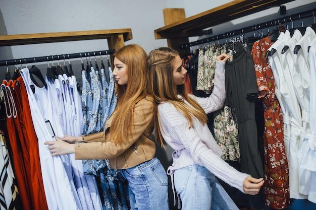 Belle ragazze allo shopping scegliendo i vestiti nel negozio