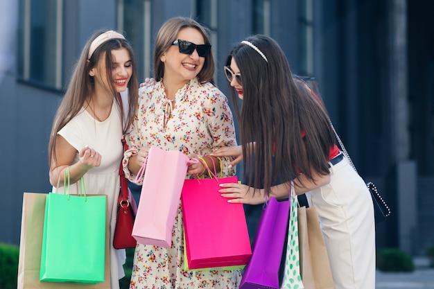 Belle ragazze che camminano per la città dopo lo shopping. tre donne tengono in mano borse della spesa colorate. consumismo, acquisti, vendite, stile di vita.