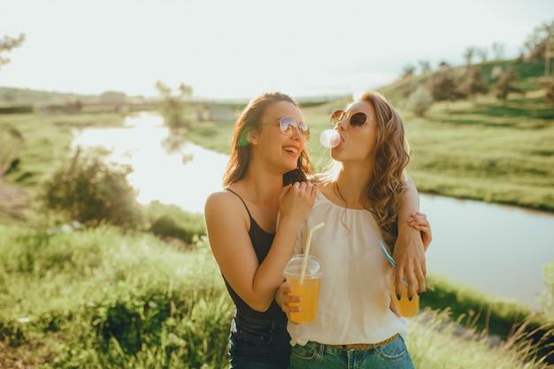Belle ragazze che fanno scoppiare una bolla da una gomma da masticare, divertirsi, bere succo d'arancia dal bicchiere di plastica, estate, al tramonto, espressione facciale positiva, all'aperto