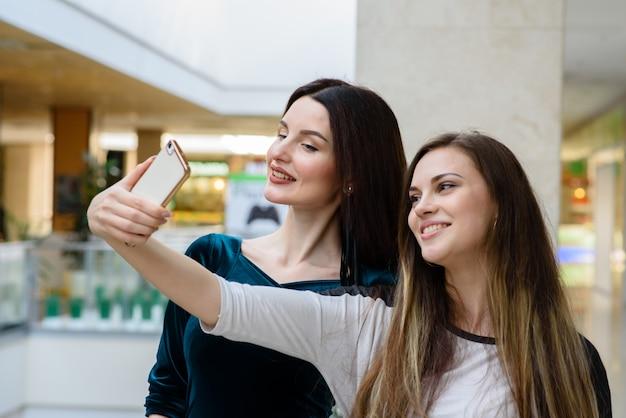 Belle ragazze che fanno selfi al centro commerciale.