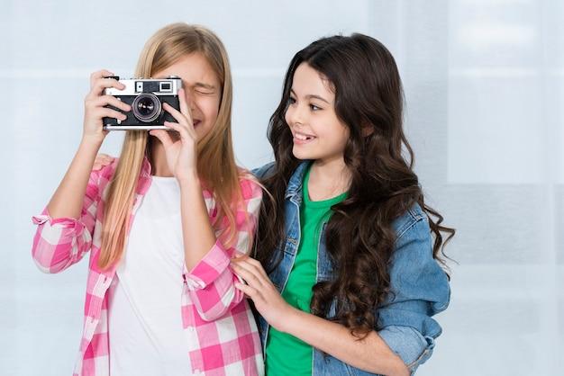 Belle ragazze che usano la macchina fotografica