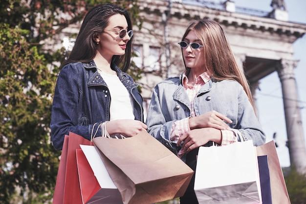 Belle ragazze con le borse della spesa che camminano al centro commerciale.