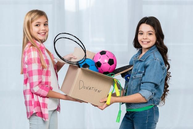 Belle ragazze con scatola di donazione