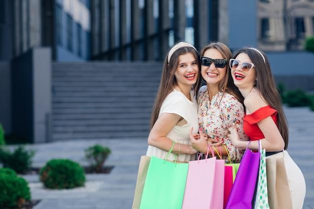 Belle ragazze dopo lo shopping tre donne tengono in mano i sacchetti della spesa colorati. consumismo, acquisti, vendite, stile di vita.