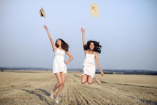 Belle ragazze eleganti in un campo di grano in autunno