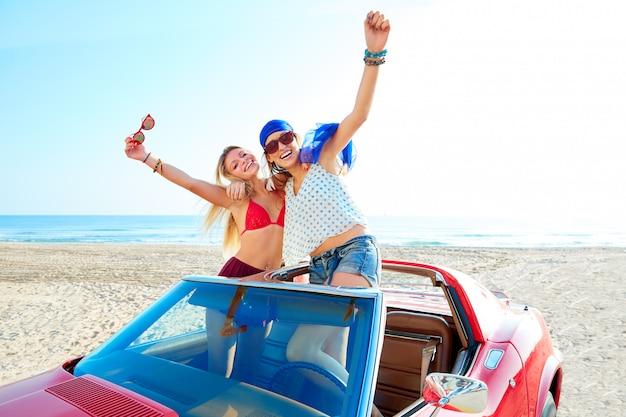 Belle ragazze festa ballando in una macchina sulla spiaggia