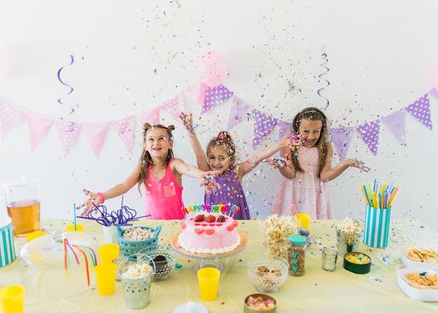 Belle ragazze godendo la festa di compleanno a casa con varietà di cibo e succo sul tavolo