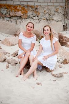 Belle ragazze in abiti bianchi fotografati sul mare