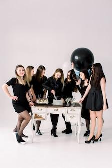 Belle ragazze in abiti neri festeggiano il compleanno o il addio al nubilato, una ragazza taglia la torta, si diverte. tavolo decorato con mongolfiere, torte, bevande e dessert