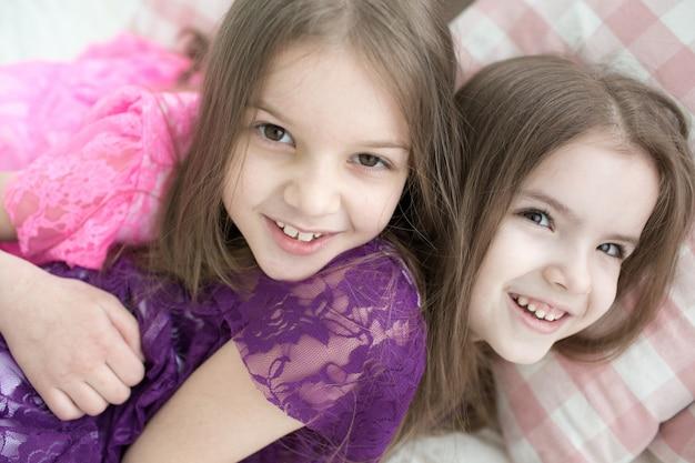 Belle ragazze in abiti rosa e viola giacevano a letto